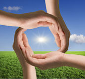 Circle of hands against blue sky Royalty Free Stock Images