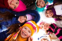 Circle of happy kids outside. Group of happy kids look down wearing winter clothes stock photography