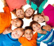 Circle of happy kids together smiling. Circle of smiling positive kids looking down - diversity group of boys and girls Royalty Free Stock Image