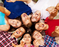 Circle of happy teenagers. Circle of happy smiling teenage school friends lying on the grass Royalty Free Stock Photo