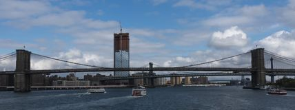 Circle line and other tour boats heading under the Brooklyn Brid. New York City, USA - 15 October 2017: Tour party boats bringing tourists to the bridges and Royalty Free Stock Photography