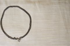 A circle made of a female, beautiful, silver chain. On a beige background Royalty Free Stock Image