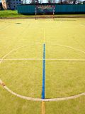 Circle in middle of court. Empty outdoor handball playground, plastic light green surface Stock Photos