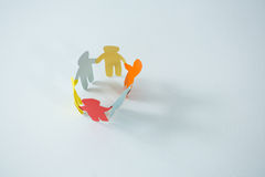 Circle of multicolored paper cut-out figures. On white background Stock Photography