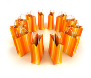 Circle of orange striped shopping bags. 3D rendering of yellow striped shopping bags forming a circle against a white background Royalty Free Stock Photography