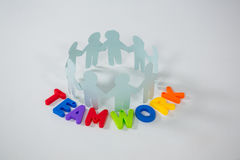 Circle of paper cut-out figures with teamwork word. On white background Royalty Free Stock Photography