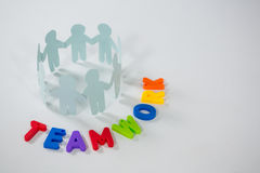 Circle of paper cut-out figures with teamwork word. On white background Royalty Free Stock Photos