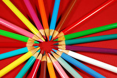 Circle of pencil crayons. Circle of colorful pencil crayons on red background Royalty Free Stock Image