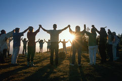 Circle of people holding hands. With arms up at Earth Day Ceremony as sun sets royalty free stock photos