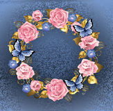 Circle of pink roses. Round wreath of pink roses, violets blue, gold jewelery and blue leaves with blue butterflies on a blue background brocade. Design of roses Royalty Free Stock Photography