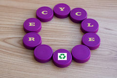 A circle of plastic caps, with the logo of recycling,as a backdrop royalty free stock photo