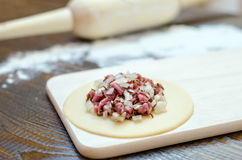 Circle of raw dough with meat and onions, on a wooden board, rolling pin and flour. On a brown wooden background Stock Images