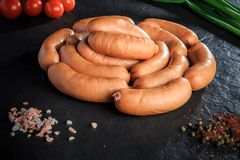 Circle of raw short thick sausages on black background. Circle of raw short thick meat sausages served with spices, green onion and tomatoes cherry on black stock image