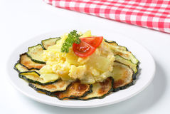 Circle of roasted zucchini slices with potatoes and fried eggs Stock Photos