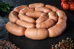 circle set of raw short sausages with rucola and tomatoes royalty free stock photos