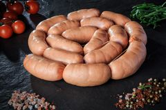 Circle set of raw short sausages with rucola and tomatoes. Circle set of raw short thick sausages served with salt, spices, green rucola, and tomatoes cherry on royalty free stock photos