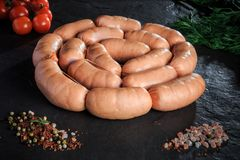 Circle set of raw short sausages with rucola and tomatoes. Circle set of raw short thick sausages served with salt, spices, green rucola, and tomatoes cherry on stock photography