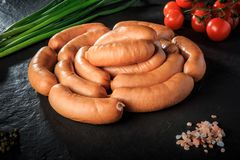 Circle set of raw short sausages with salt, onion and tomatoes stock images