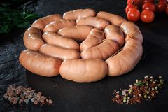 Circle set of raw short sausages with rucola and tomatoes. Circle set of raw short thick sausages served with salt, spices, green rucola, and tomatoes cherry on royalty free stock images