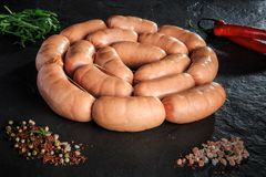 Circle set of uncooked short sausages with rucola and chili. Circle set of uncooked short thick sausages served with pink salt, spices, rucola and red chili stock photos