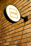 Circle shape ATM sign. On brick wall royalty free stock photography