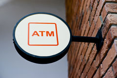 Circle shape ATM sign. On brick wall stock photography