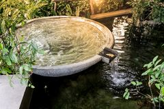 Circle shape water fountain and water fall in garden or park. Royalty Free Stock Image