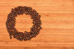 Circle shaped coffee beans over bamboo wood background Royalty Free Stock Image