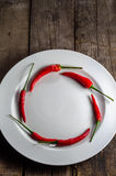 Circle shaped red chilies on plate. A combination of red and green colors of chilies and plate Royalty Free Stock Photography