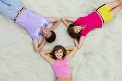 Circle of teens. Above angle of happy teenage friends lying on sandy beach Stock Photography