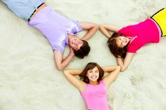 Circle of teens. Above angle of happy teenage friends lying on sandy beach Royalty Free Stock Photos