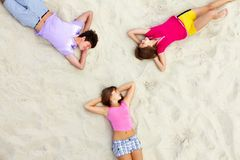 Circle of teens. Above angle of happy teenage friends lying on sandy beach Stock Photos