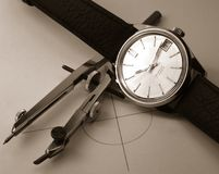 Circle time. Classic dress watch and compas over a circle monochrome stock image