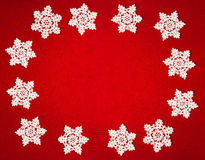 Circle of twelve white crochet snowflakes on red felt background Stock Photo