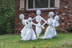 A circle of white clad ghosts play a game. Of ring around the rosie, as they dance on the lawn of a home decorated for Halloween royalty free stock photos