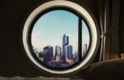 Circle window with modern buildings in the city at morning Royalty Free Stock Image