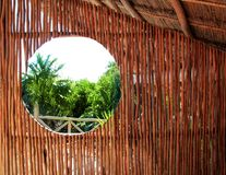 Circle window wooden cabin tropical Jungle. Circle window in wooden sticks cabin with tropical Jungle background Stock Photo