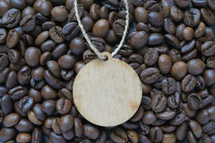 Circle wooden tag lay on coffee beans Stock Images