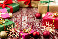 Circle of Xmas Gifts Around Central Void. Circular arrangement of plain Christmas presents wrapped in green, red, magenta and gold. Depth of field cutting across Royalty Free Stock Images