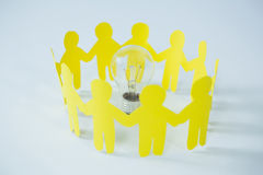 Circle of yellow paper cut-out figures and light bulb. On white background Stock Image