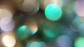 Circles Bokeh Rotation in a Clockwise. The Circles Bokeh stock video features a circle rotation in a clockwise direction of blurred gold, turquoise and violete Stock Images