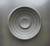 Circles door. A heavy circular door handle on a brushed metal door royalty free stock photo