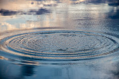 Circles  and reflection of sky on the water surface of a lake Stock Photo