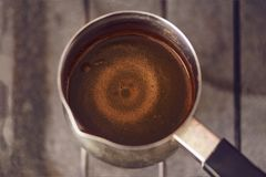 Black coffee is boiled in coffee pot. Circles on the surface of black coffee brewed in coffee pot, soft focus, toned Royalty Free Stock Photography