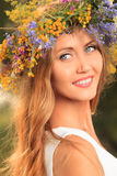 Circlet of flowers. Portrait of a romantic smiling young woman in a circlet of flowers outdoors Stock Photos