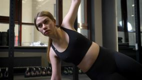 Circlind aroung view of concentrated sportsgirl standing in side plank with her phone lying nearby in gym. stock footage