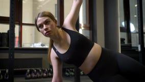 Circlind em torno da ideia do sportsgirl concentrado que está na prancha lateral com seu telefone que encontra-se próximo no gym filme