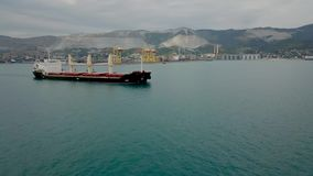 Circling the vessel in the incoming city leaving the port of Novorossiysk in the daytime. Ship carrying bulk cargo. Circled the ship. He reached the ship stock footage