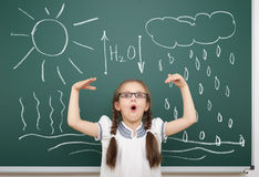 Circolazione dell'acqua del disegno della ragazza sul consiglio scolastico Immagine Stock