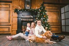 Circolo famigliare di Natale e del nuovo anno di tema Giovane famiglia caucasica con il golden retriever di 1 anno di Labrador de fotografia stock